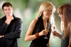 Two women holding glasses with champagne and laughing, young man looking at them and smiling, outdoors, focus on women